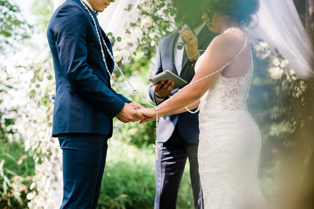 Bride and groom wrapped in rosary holding hands during prayer
