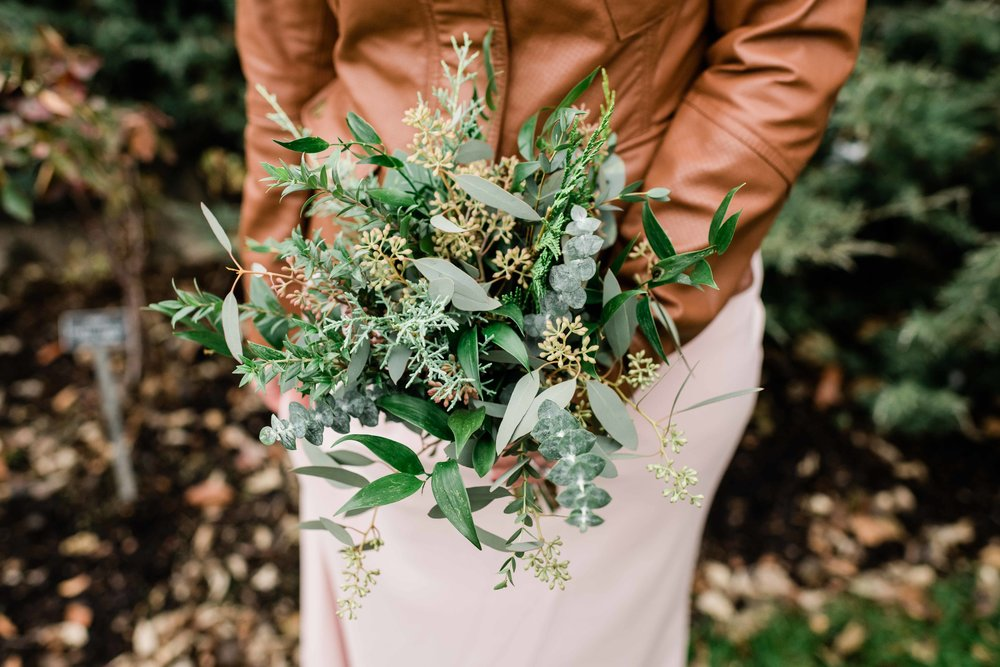 Bridesmaid in leather jacket holds bouquet