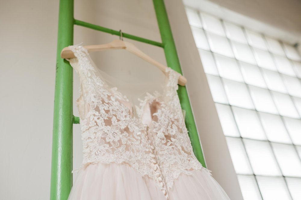 Bridal gown hanging on ladder