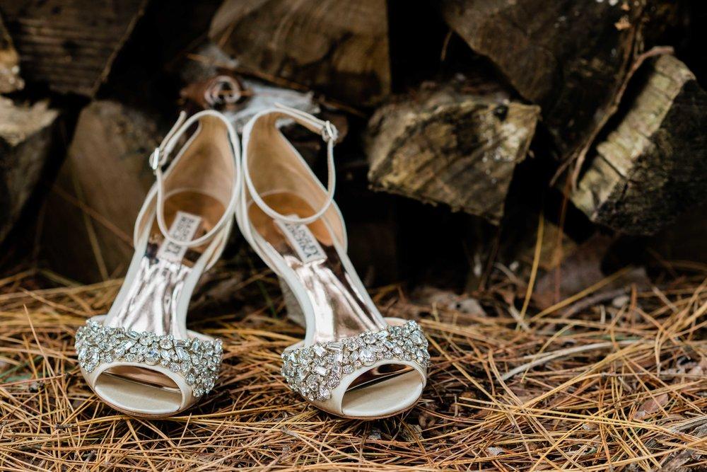 Badgley Mischka bridal shoes sitting on pine needles