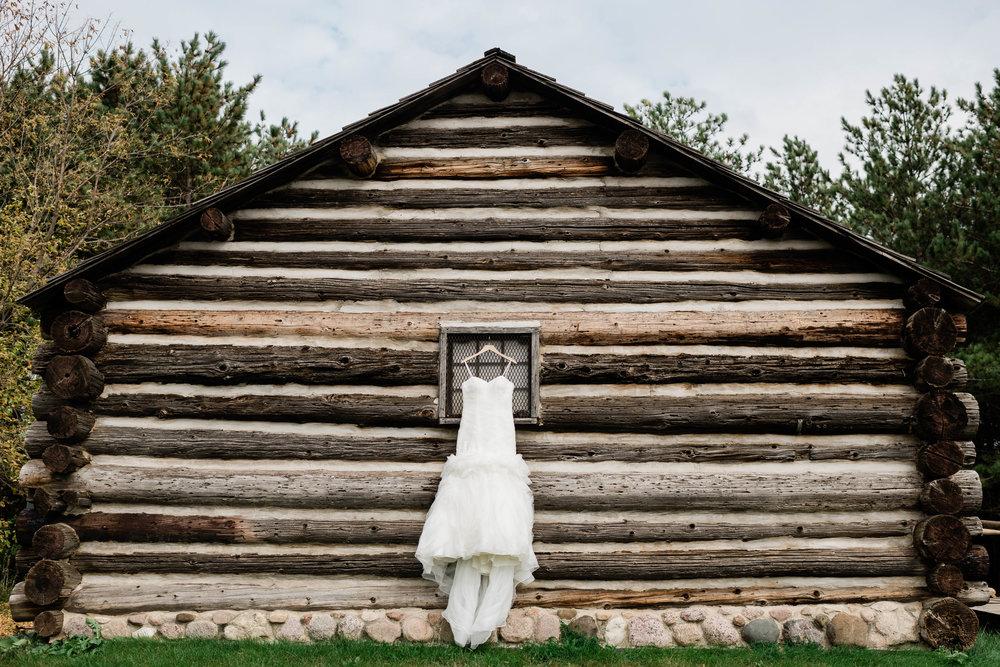 Wedding dress hanging on log cabin