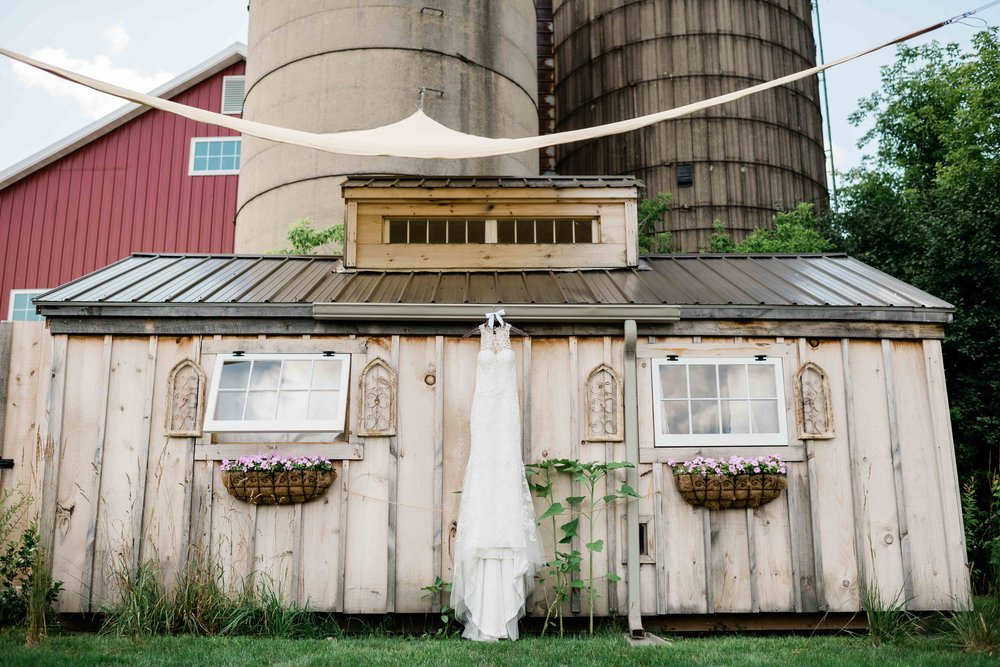 Wedding dress hanging from She Shed at Cupola Barn
