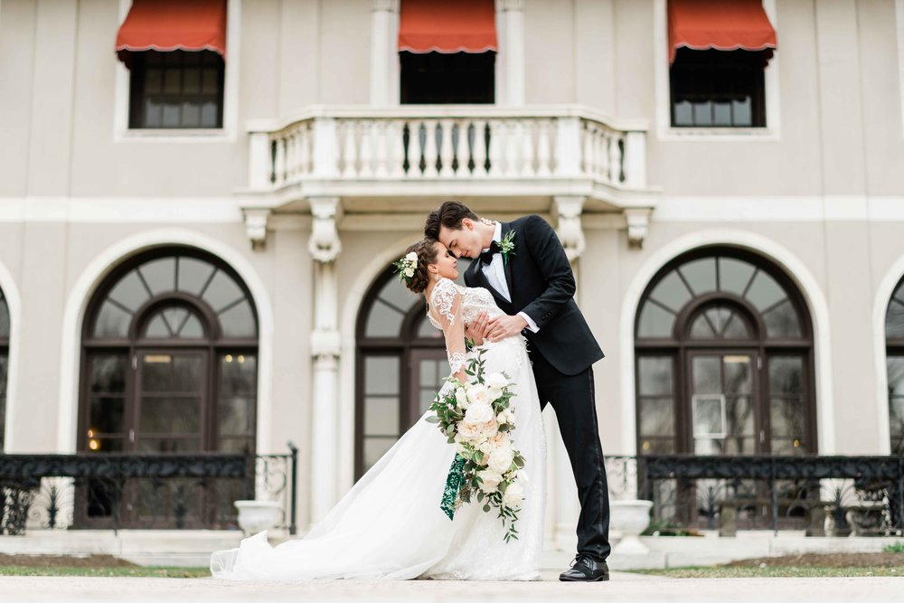 Groom dips bride back and kisses her