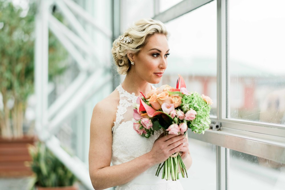 Bride looking out window with her bouquet