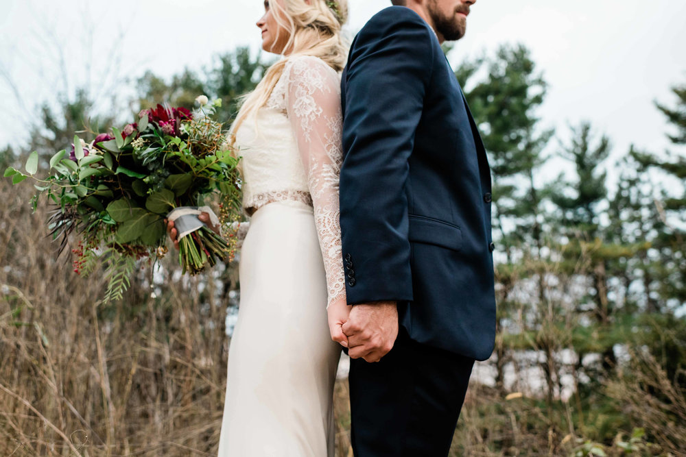Bride and groom back to back holding hands