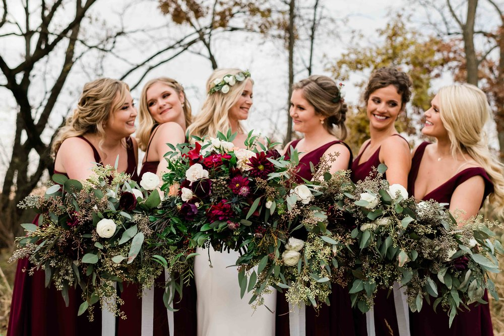 Bride and bridesmaids smile at each other as they hold out their bouquets