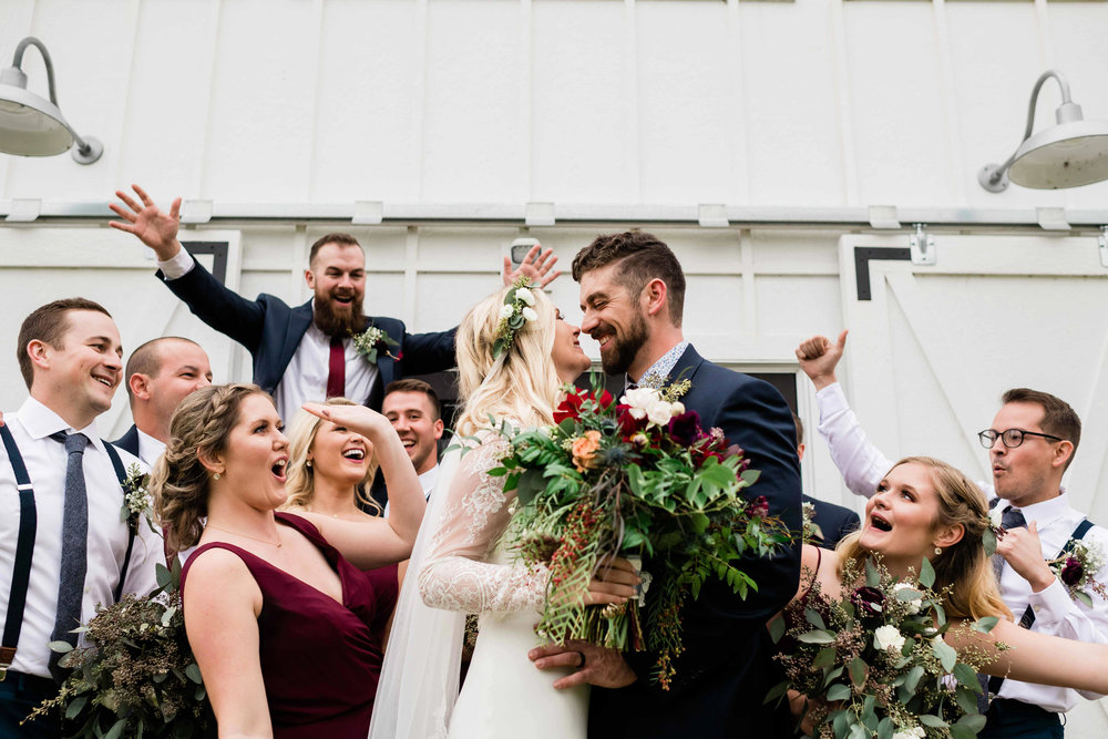 Wedding party cheering on bride and groom kissing