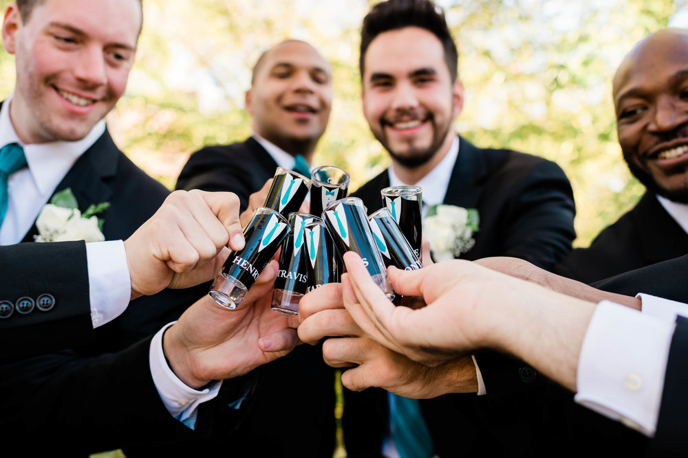 Groom and groomsmen raise their personalized shot glasses