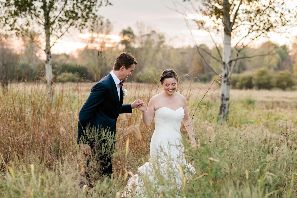 Bride and groom holding hands and strolling through a field