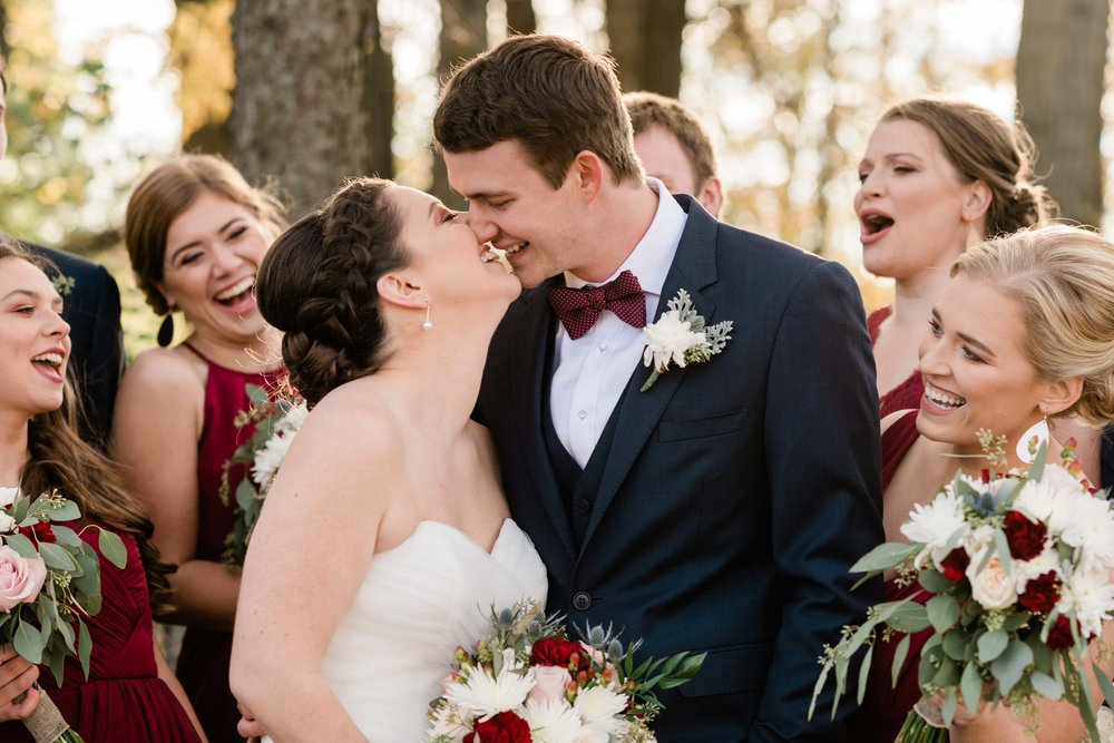 Bride and groom kiss as wedding party cheers them on