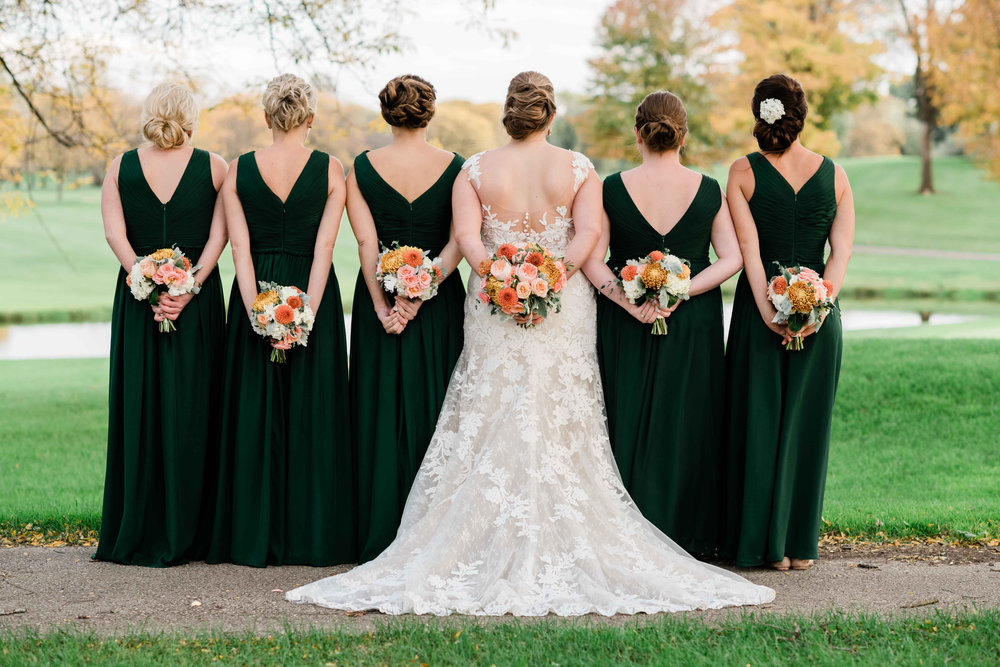 Bridesmaids holding their bouquets behind them