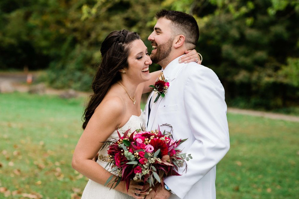 Bride and groom laugh as they embrace each other