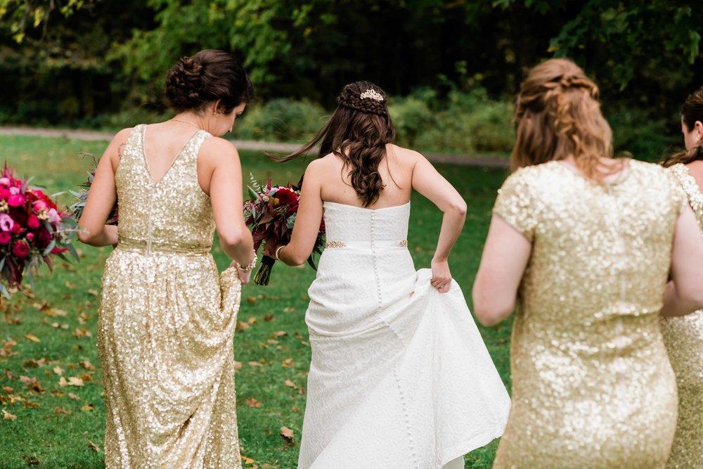 Bride and bridesmaids walking through grass