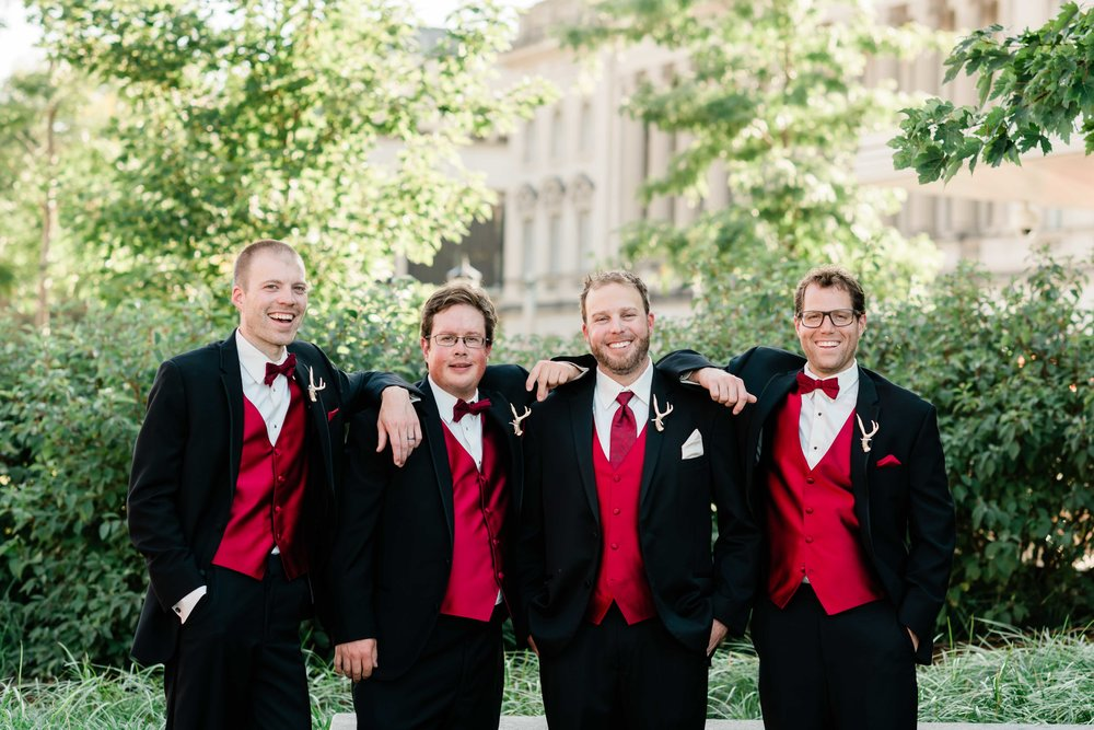 Groom and groomsmen rest their arms on each other's shoulders