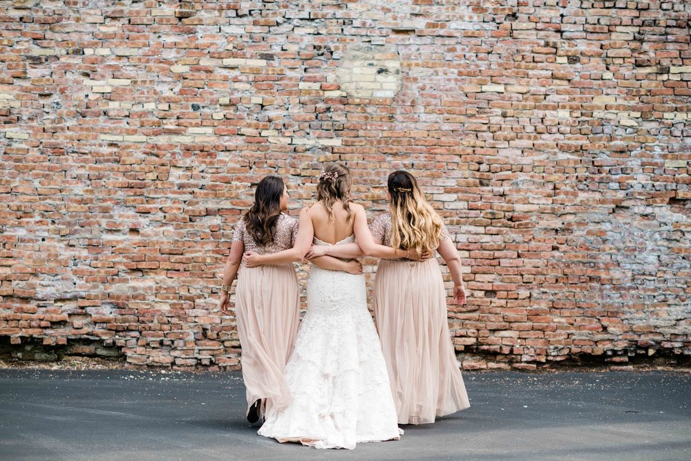 Bride and bridesmaids walk with arms around each other