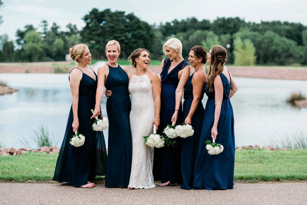 Bride and bridesmaids hold bouquets down as they laugh with each other