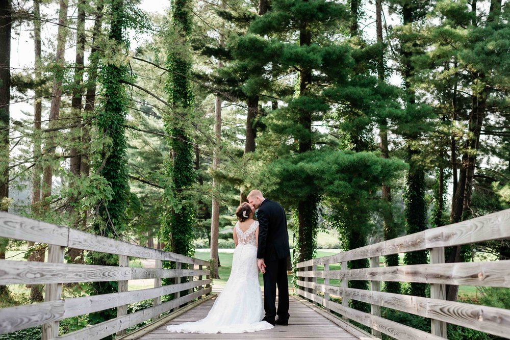 Bride and groom kissing on a bridge