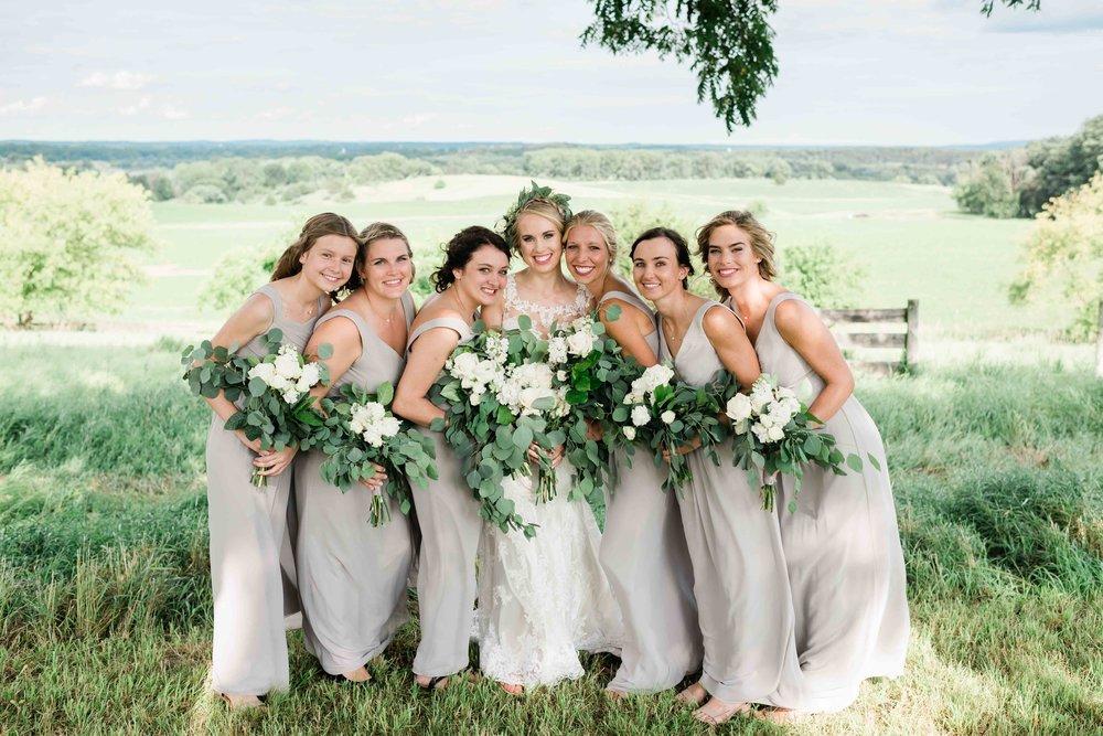 Bridesmaids lean into bride