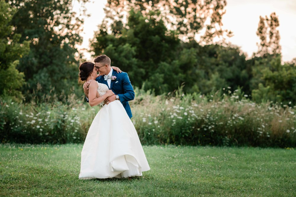 Bride and groom kissing and leaning back