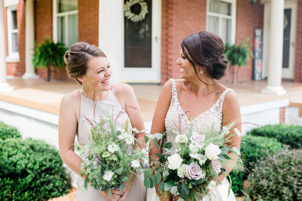 Bride and bridesmaid look at each other and laugh