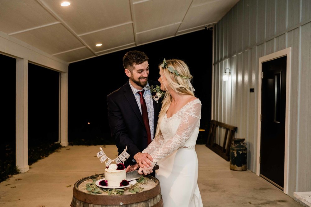 Bride and groom cut their cake outside