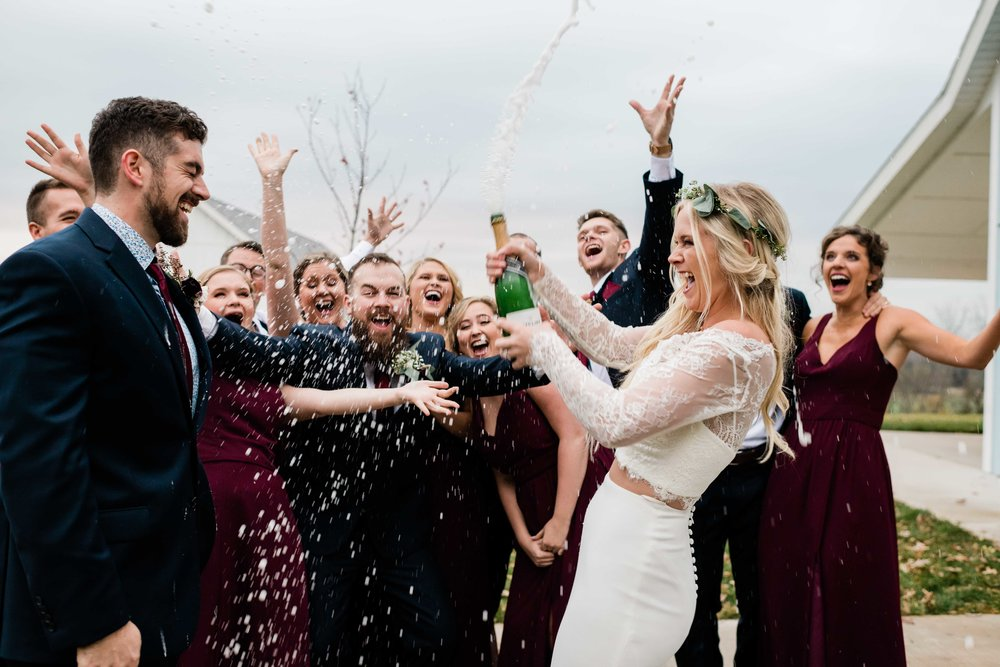 Bride opens champagne and it sprays all over wedding party
