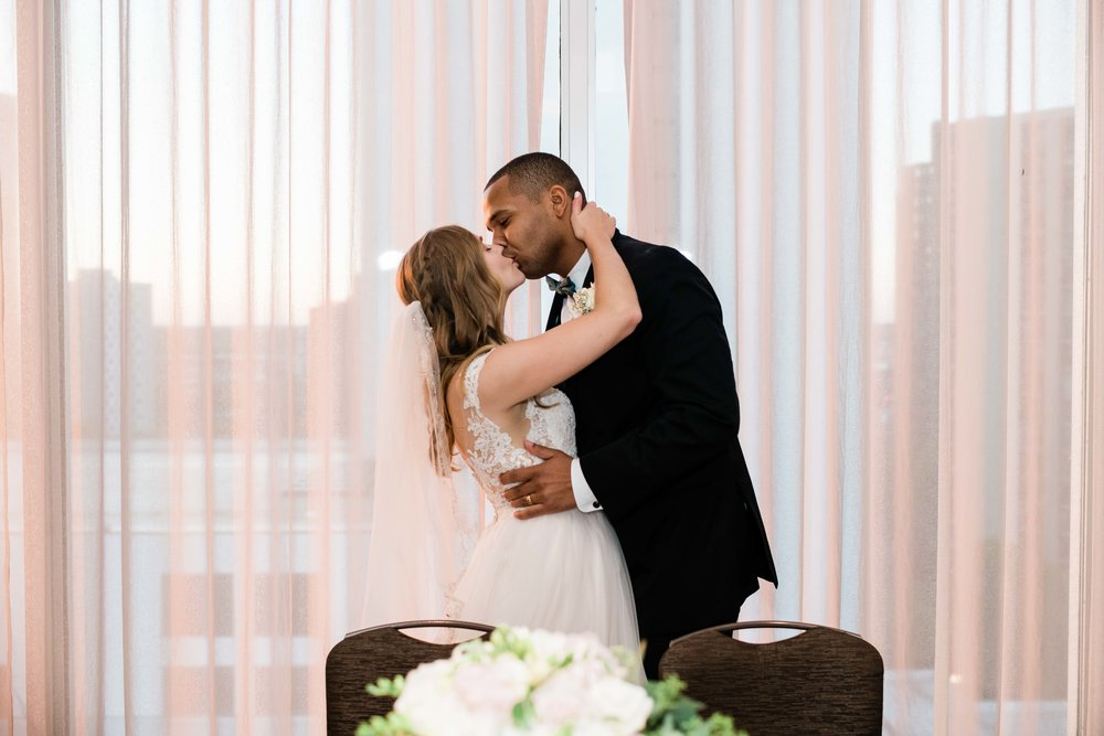 Bride and groom kiss at sweetheart table