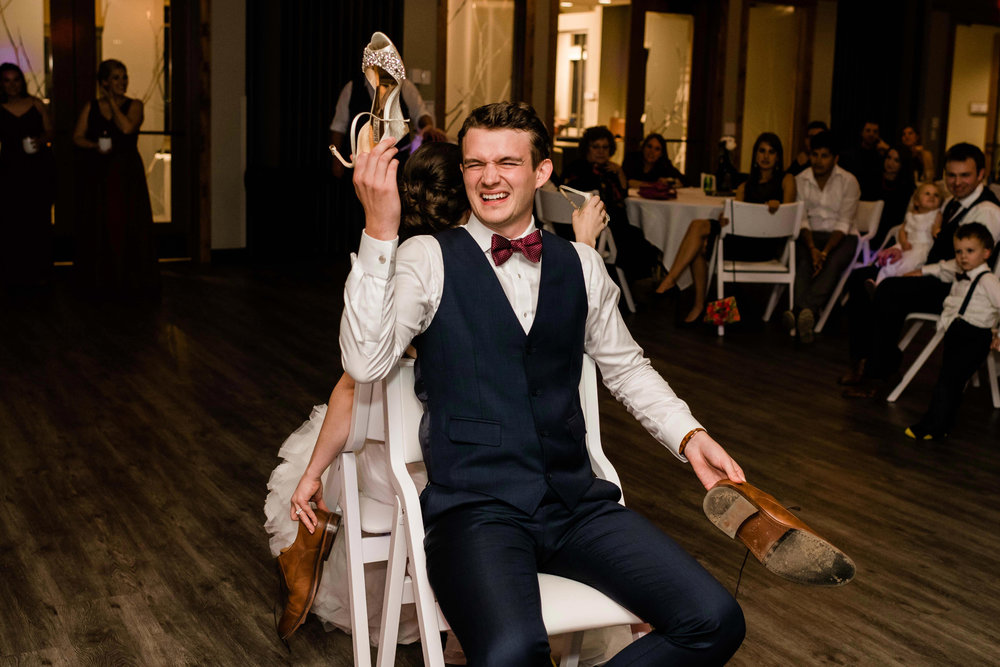Groom playing the shoe game with bride