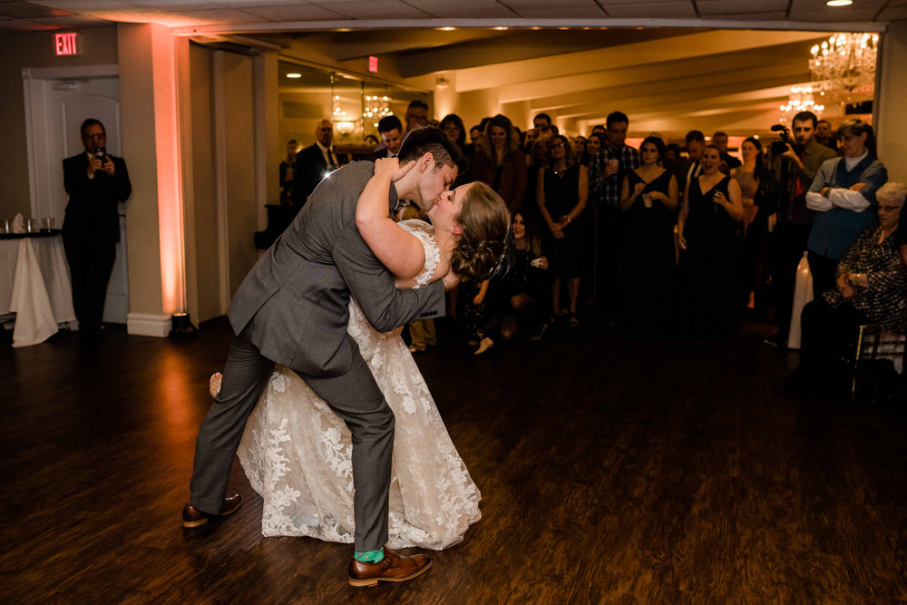Groom dips his bride back during their first dance