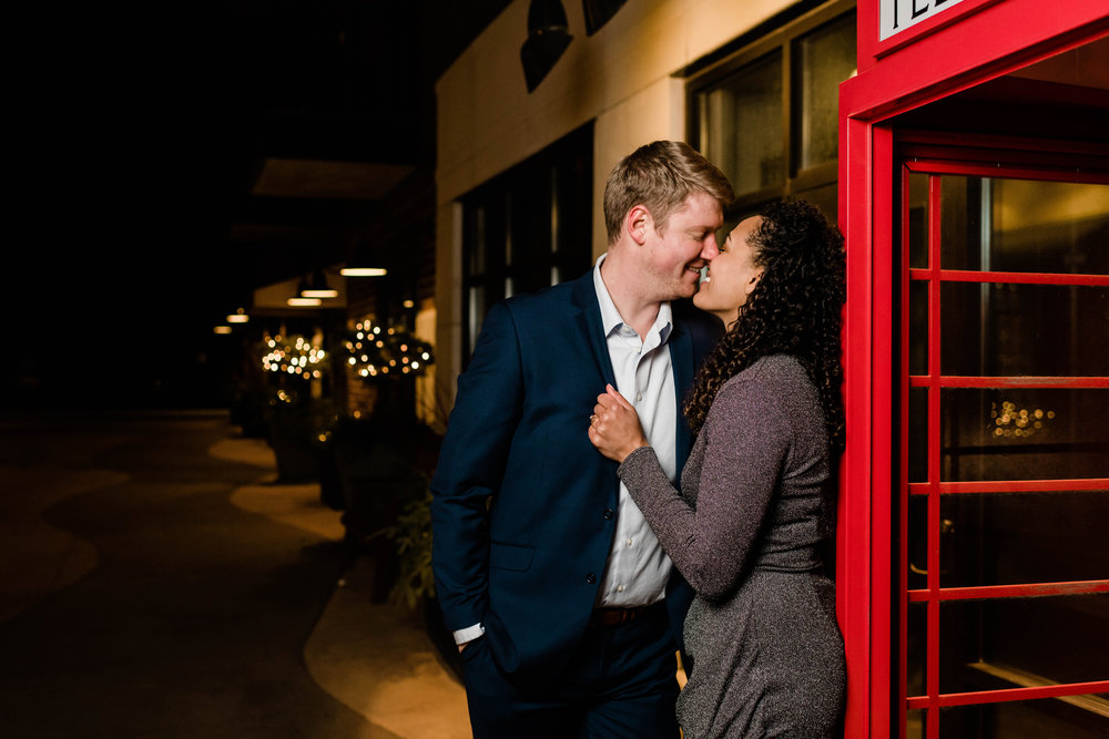 Engaged couple lean against red telephone booth