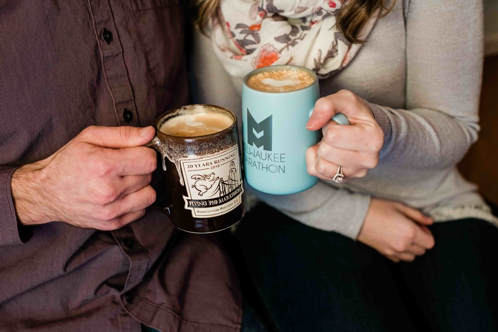 Engaged couple holds coffee mugs