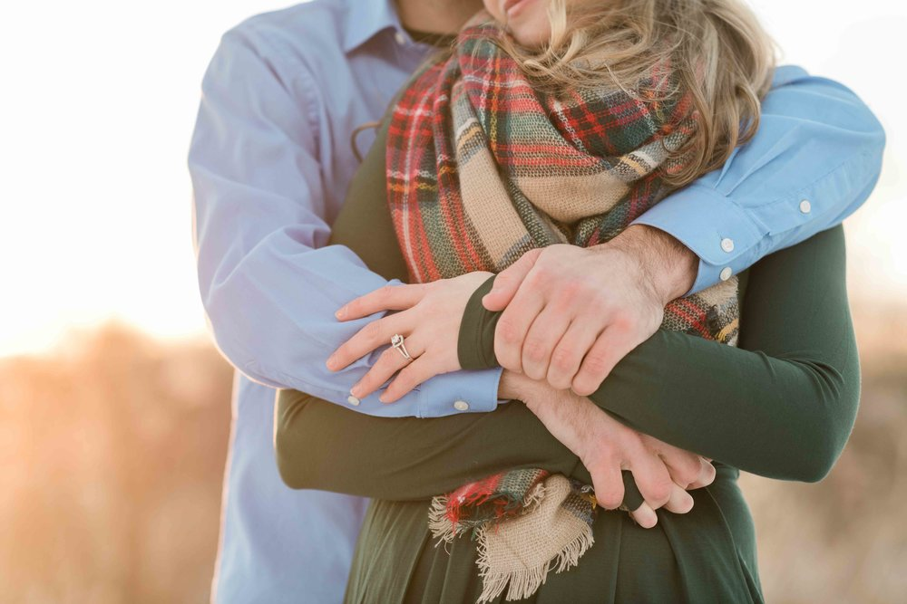 Man wraps his arms around his fiancé to warm her up