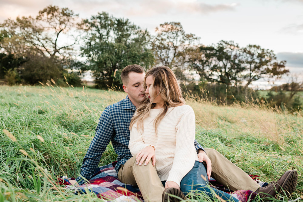 Engaged couple sits on a picnic blanket