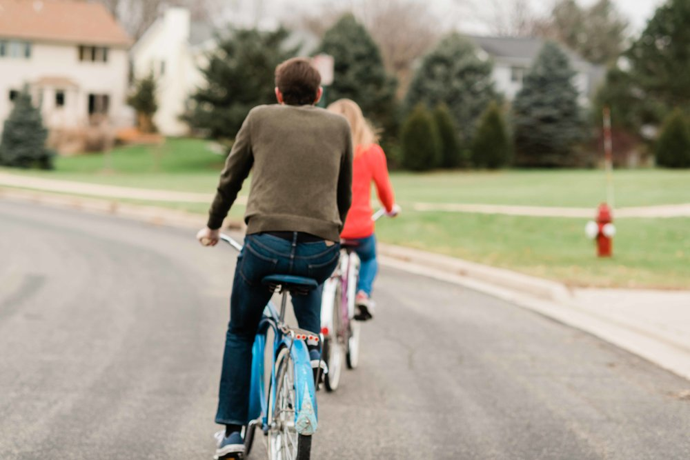 Engaged couple riding bikes