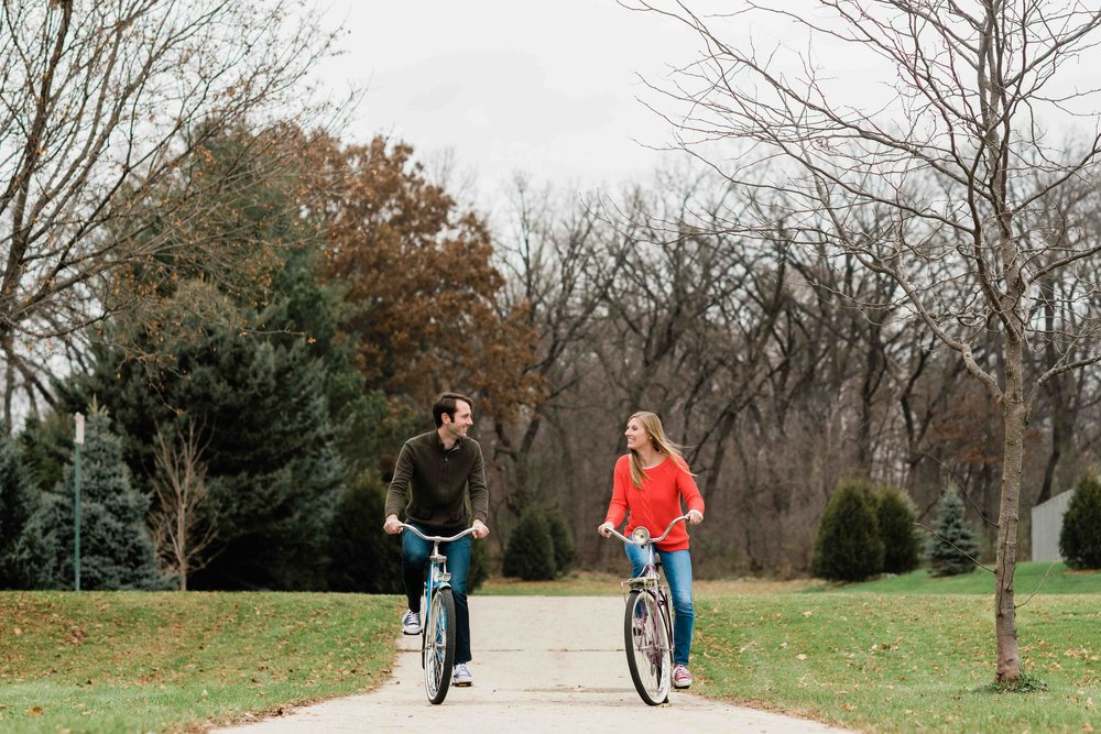 Engaged couple looks at each other as they ride bikes