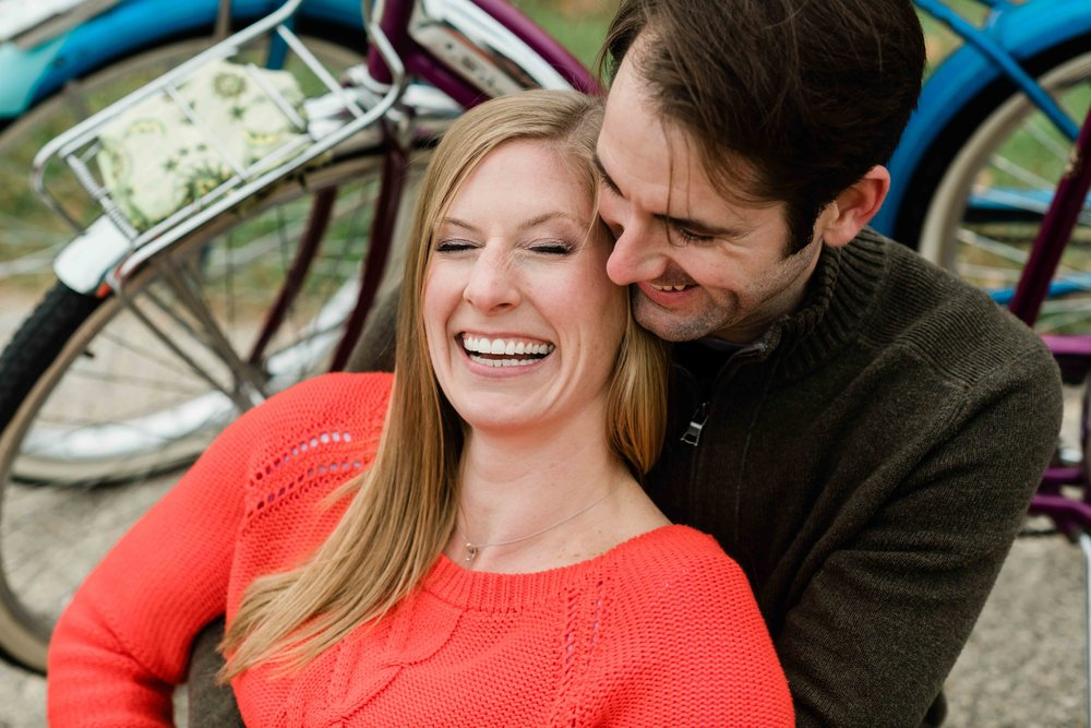 Engaged couple sitting next to their bikes and laughing