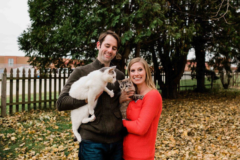 Engaged couple holding their cats