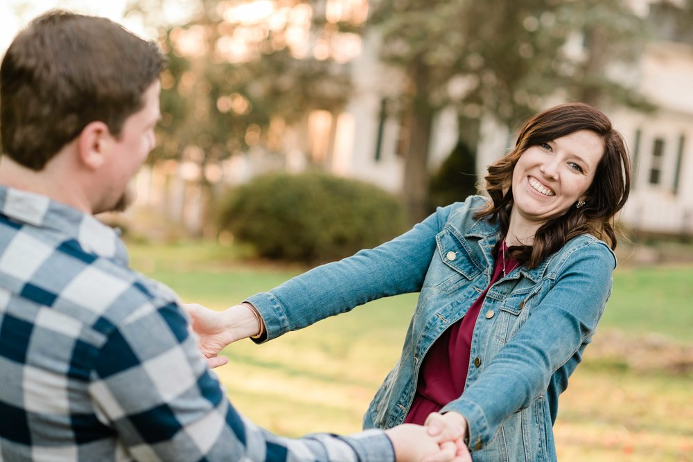 Woman leans back and smiles as her fiancé holds her by the hands
