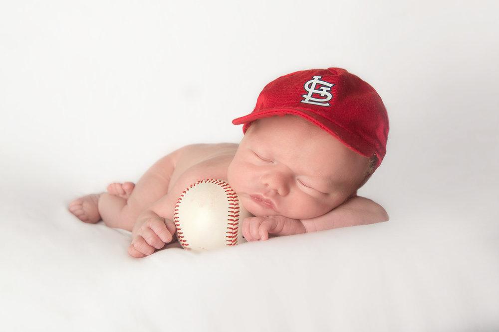 st-louis-newborn-photography-cardinals-baseball-hat-and-ball-on-white.jpg