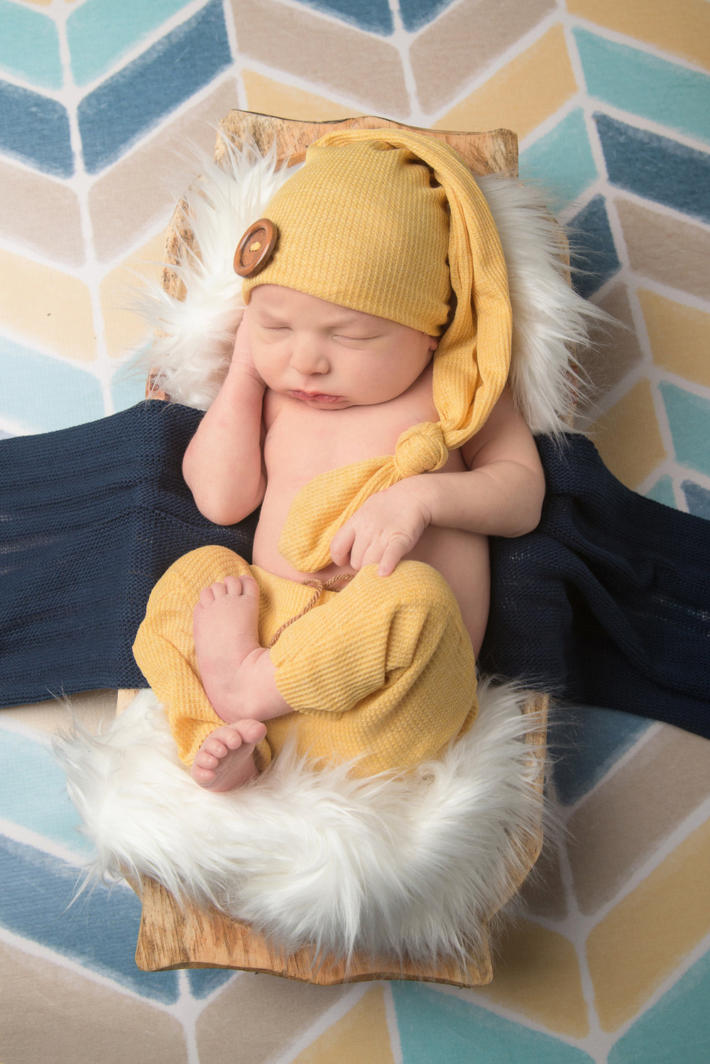 st-louis-newborn-photography-baby-boy-yellow-outfit-and-hat-blue-arrow-background-in-basket.jpg