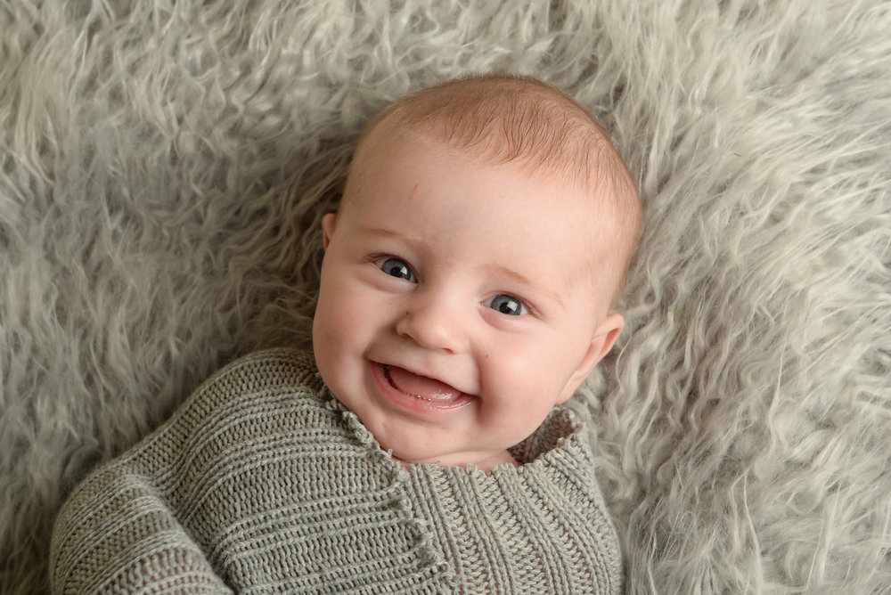 st-louis-photography-studio-three-month-milestone-session-boy-on-gray-fur-with-grey-wrap-smiling.jpg