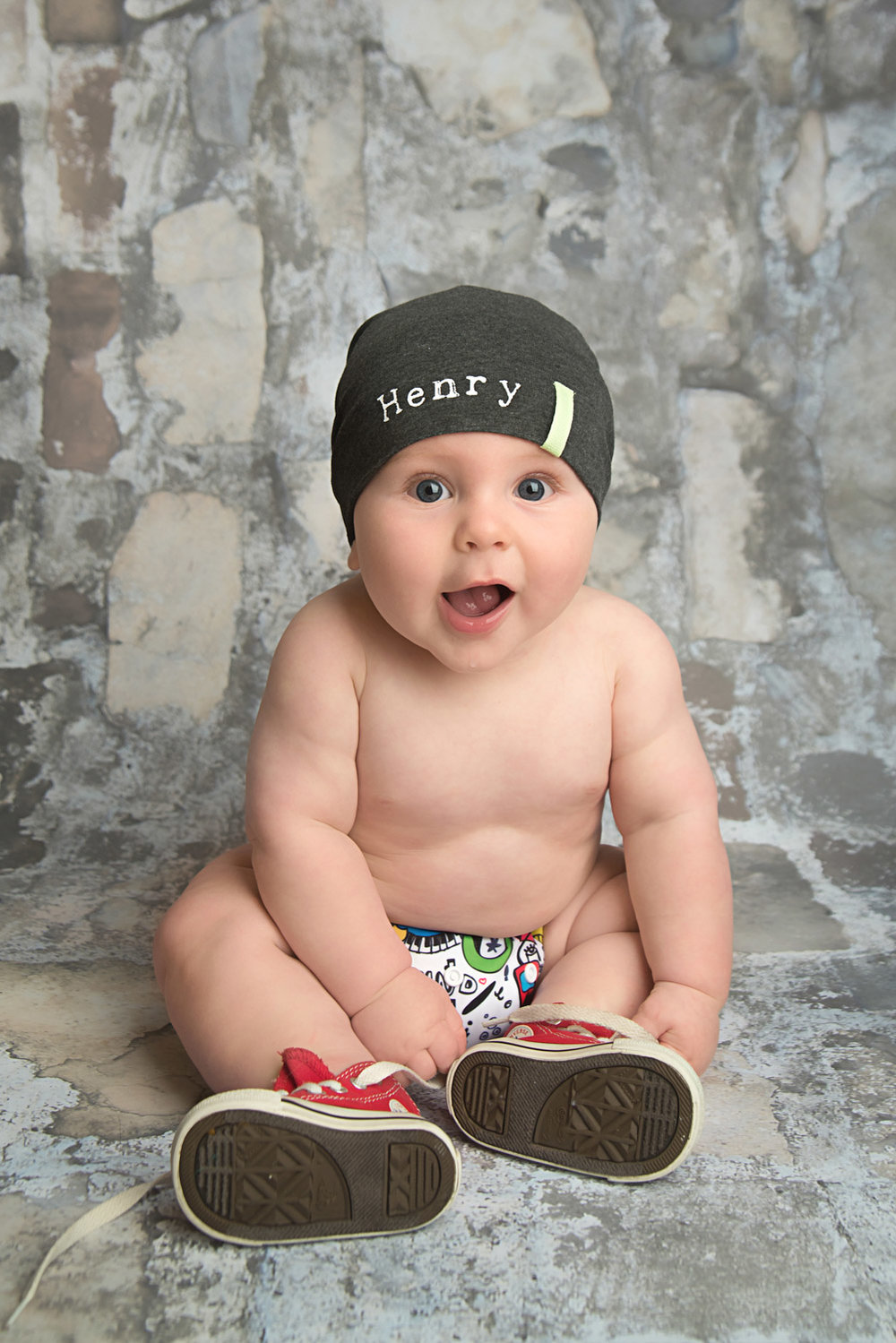 st-louis-baby-photography-studio-6-month-boy-in hat-diaper-and-converse-shoes-on-grey-brick-backdrop.jpg