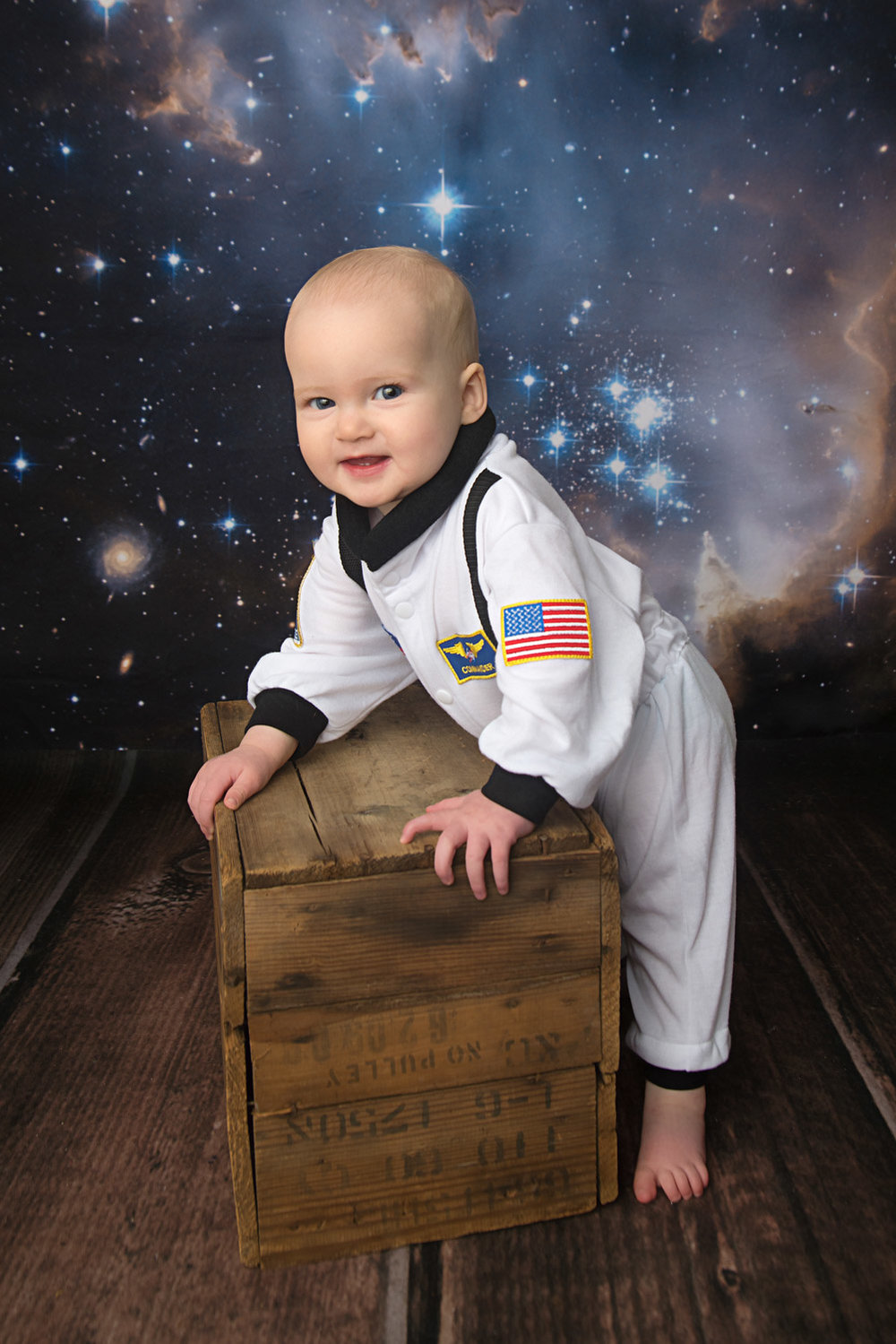 st-louis-baby-photography-studio-9-month-girl-in-nasa-suit-on-galaxy-backdrop.jpg