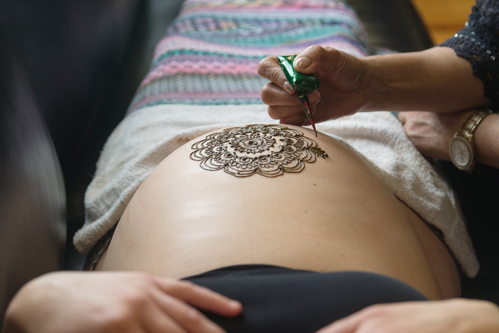 st-louis-maternity-henna-photography-close-up-of-henna-being-applied-to-belly.jpg