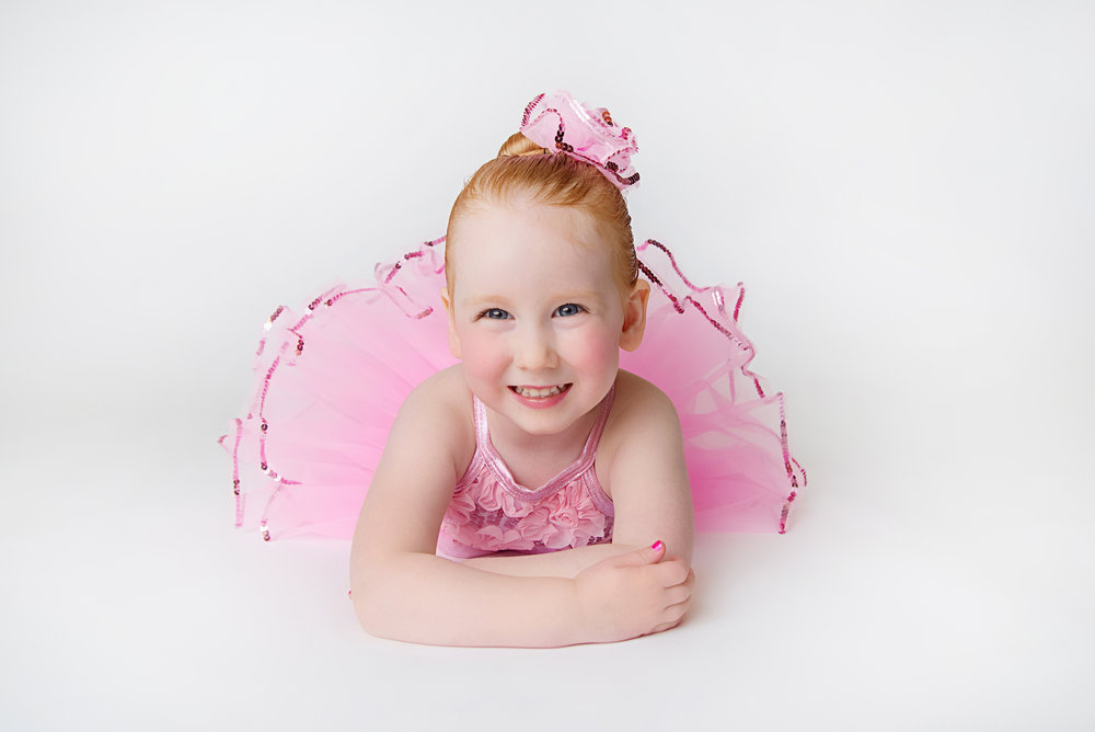 st-louis-childrens-photographer-three-year-old-girl-on-tummy-in-pink-dance-outfit-on-white-backdrop.jpg
