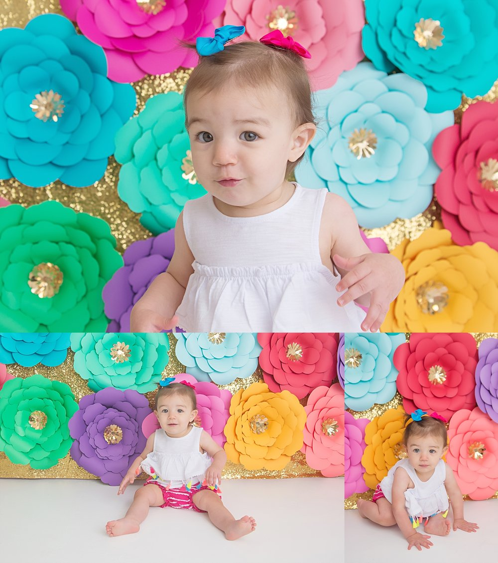 st-louis-first-birthday-cake-smash-photographer-one-year-girl-in-white-shirt-with-muli-color-paper-flower-backdrop.jpg