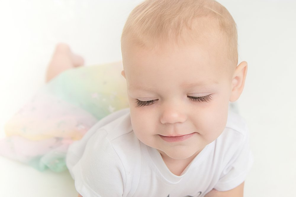 St-Louis-first-birthday-photographer-one-year-old-girl-with-pastel-rainbow-skirt-showing-eyelashes.jpg