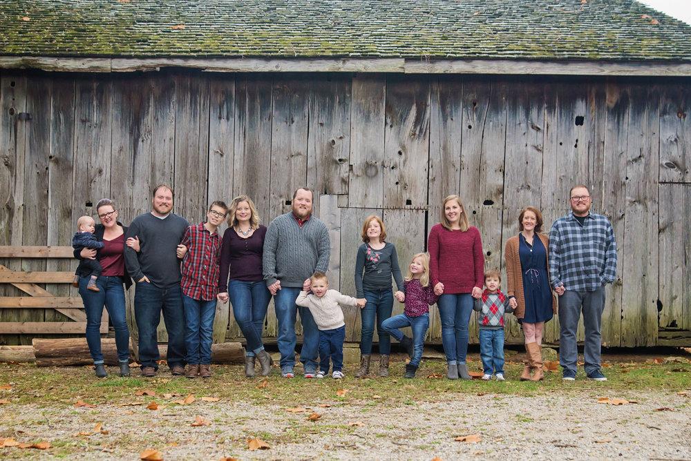 st-louis-family-photogrpaher-extended-family-session-family-standing-along-barn-at-faust-park.jpg
