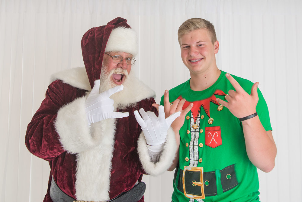 st-louis-photography-studio-sessions-with-santa-2018-santa-doing-devil-horns-with-teenager.jpg