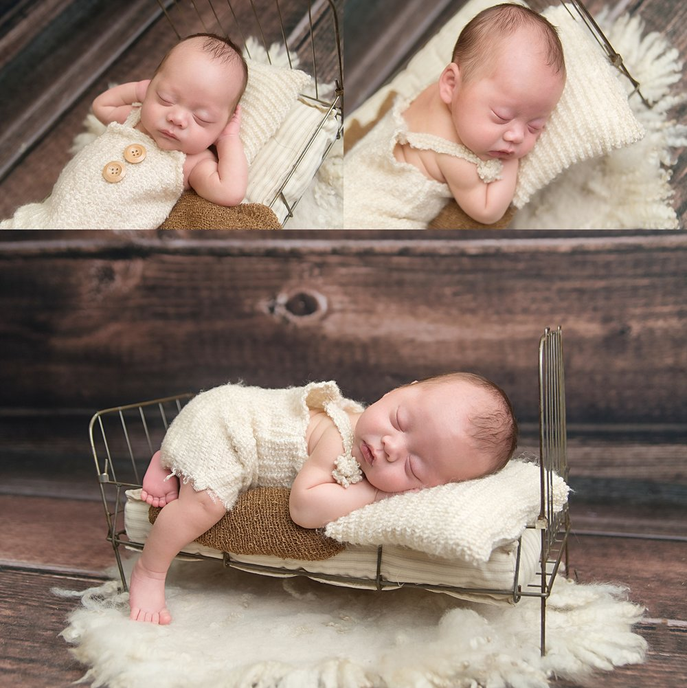 st-louis-newborn-photographer-baby-boy-wearing-fuzzy-cream-romper-laying-on-wire-bed-with-wood-backdrop.jpg